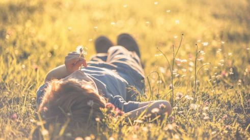 baby-lying-on-the-field-with-dandelion-in-hand